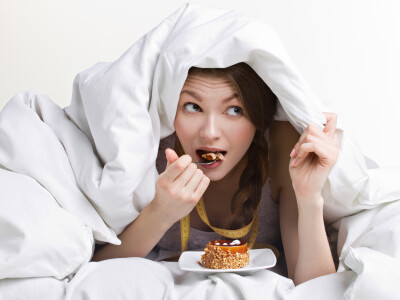 young beauty woman eating dessert under cover on white background